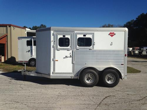CONSIGNMENT: 2003 Hart (2) horse slant load bumper pull trailer with a tack room, (2) removable saddle racks, bridle hooks, clothing rod and a spare tire.   The horse area has an interior height of 7' tall x 7' wide, insulated roof, escape door with a drop down window, drop down windows at the horses heads,  sliding bus windows at the horses hips, roof vents, rubber lined walls, rubber mats over all aluminum floor, collapsible rear tack and double back rear doors!  Clean.