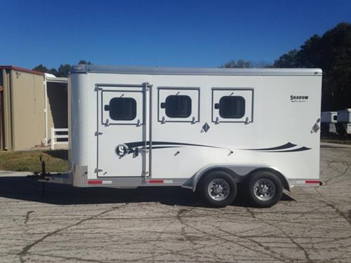 "2015 Shadow (3) horse slant load bumper pull trailer with a tack room that has a (3) tier removable saddle rack, bridle hooks and a spare tire.  The horse area has an interior height of 7'6"" tall x 7' wide x 16' long, escape door, drop down windows with drop aluminum bars at the horses head and hips, insulated roof, roof vents, rubber mats over all aluminum floor, collapsible rear tack with a (3) tier swing out saddle rack and double back rear doors!  This trailer is like new."
