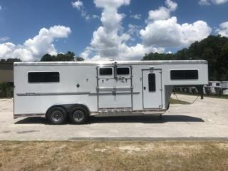 "CONSIGNMENT: 2009 Shadow (2+1) trailer with a tack room that has saddle racks, bridle hooks and a brush box.  The horse area has an interior height of 7'6"" tall x 7' wide, escape door with a drop down window, side ramp with dutch doors, insulated roof, center airflow gate, rubber mats over aluminum floor, removable divider, makes into 2 box stalls and a rear ramp with dutch doors!  Clean."