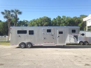 NOW $27,900!!! 2017 Kiefer Ext (2) + (1) GN Trailer with an interior height of 8' tall x 7' wide x 24' long, tack room with removable saddle racks, bridle hooks, fully lined & insulated, carpet, brush box and a walk thru door into the horse area. In the horse area you have a fully lined & insulated roof, roof vents, escape door with a drop down window, drop down windows at the horses head, side ramp with dutch door, air flow center gates, removable divider,