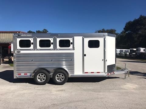 "2019 Cimarron (3) horse slant load bumper pull trailer with the ""Ready to Go"" Package that has a swing out (3) tier saddle rack, bridle hooks, hat shelves, clothe bar, swing out blanket rack, 25 gallon water tank and a door caddy. In the horse area you have an interior height of 7' tall x 7' wide, escape door with a drop down window and drop down aluminum bars, drop down windows at the horses heads with drop down aluminum bars,"
