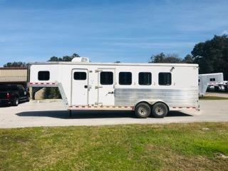 2005 Kiefer Built (3) horse living quarter trailer with a 6' Conversion that has an A/C unit, countertop space, sink, microwave, 3cu fridge, cabinets, closets, shower and a toilet.   The horse area has an interior height at 7' tall 7' wide, drop down windows at the horses heads with drop down aluminum bars, roof vents, rubber mats, air flow dividers, rear collapsible tack room with saddle racks, bridle hooks and double back rear doors!  The exterior has a hydraulic jack and spare tire.