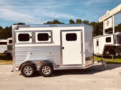 "2020 Cimarron (2) horse slant load bumper pull trailer with the ""Ready to Go Package"" that consist of a swing out (2) tier saddle rack, bridle hooks, carpet lined tack room wall, clothes bar, 25 Gallon Water Tank, insulated roof and a door caddy!  The horse area has an interior height at 7' 7"" tall x 7'wide, drop down windows at the horses heads with drop down aluminum bars, drop down windows at the horses hips as well, insulated roof, roof vents, rubber lined & insulated walls,"