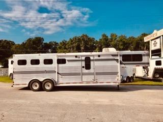1996 Sundowner (4) horse slant load weekender trailer with a 7' conversion that has a brand new A/C unit, wired for 100V, bunk beds, corner bench seat, sink, open style closets, shelves, (2) access doors on each side and a walk thru door into the horse area.