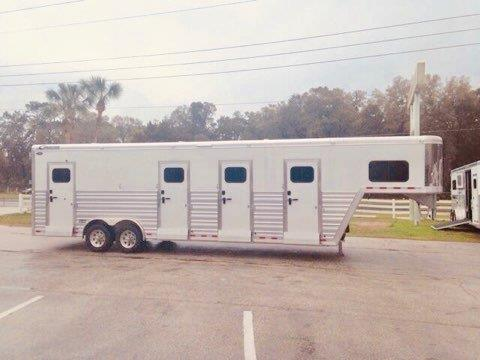 2017 Cimarron (3) box stall trailer with a front tack room that has bridle hooks and a brush box, the horse area has an interior height at 8' tall x 8' wide x 28' long, (3) escape doors for each box, insulated roof, roof vents, electric fans, full swinging solid gates, rubber lined & insulated walls, rubber mats over all aluminum floor and a rear ramp with dutch doors!  The exterior has a hydraulic jack, AIR RIDE EQUIPPED with Electric Over Hydraulic Brakes and 17.5 Aluminum Wheels.