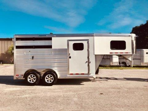 """2020 Cimarron (2) horse slant load trailer with a front tack room with the """"Ready to Go Package"""" which includes a Swing Out Saddle Rack, Bridle Hooks, Carpet Wall, Hat Shelf with Clothe Bar, Boot Box, Door Caddy and a Water Tank! The horse area has an interior height at 7'6"""" Tall x 7' Wide, Drop Down Windows at the horse heads with drop down aluminum bars, airflow divider, stock sided at hips, insulated roof, roof vents, rubber lined walls, rubber mats over all aluminum floor,"""