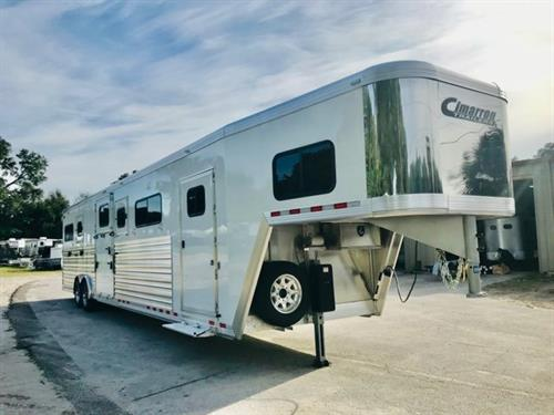 2020 Cimarron (6) horse head to head trailer with an interior height at 8' tall x 8' wide x 35' long, 6' tack room with saddle racks, bridle hooks, tack room window, brush box and a fold up step.   The horse area has 6 stalls with one large center box, can be made into a 4 horse head to head or 3 box stalls.  Has an escape door,  drop down windows at the horses heads, insulated roof, roof vents, side ramp with dutch doors, WERM FLOORING and a rear ramp with dutch doors.