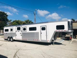 2020 Cimarron (4) horse head to head with a 5' tack room that has (4) removable saddle racks, bridle hooks and a brush box. The horse area has an interior height of 8' tall x 7' wide x 33' long, insulated roof, roof vents, rubber lined & insulated walls, removable dividers that are stored on the side of each box, two center gates with double doors making 3 box stalls, rubber mats over all aluminum floor,