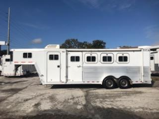 2000 Featherlite (3) horse slant load weekender trailer with a 6' conversion that has an A/C unit, fridge, microwave, sink, cabinets, stove with oven, toilet shower combo, closets and a walk thru door.