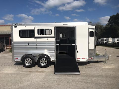 "2020 Cimarron (2) horse straight load side ramped bumper pull trailer with a front tack room that has saddle racks, bridle hooks, carpet lined walls, brush box and a window in the bulk head wall.   In the horse area you have an interior height at 7'6"" tall x 7' wide, escape door with drop down window, side ramp with dutch door, electric fans, insulated roof, roof vents, removable divider, rubber mats over all aluminum floor and a rear ramp with dutch doors!"
