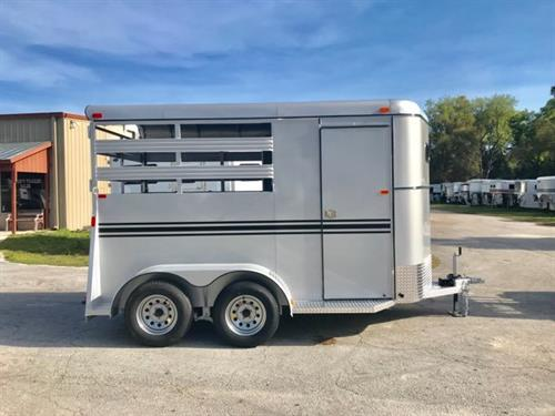 2020 Bee (2) horse slant load bumper pull trailer with a front tack room that has removable saddle racks, bridle hooks and a swinging tack room wall. The horse area has an interior height at 7'tall x 6' wide x 14' long, escape door, stock sides at the horses head and hips, air flow dividers, rubber mats over wood floor and a full swinging rear door with a half slider! The exterior has two 3500lbs axles with a spare tire. LIFETIME WARRANTY on the Floor!