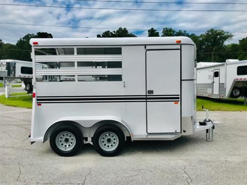 2020 Bee (2) horse slant load bumper pull trailer with a front tack room that has removable saddle racks, bridle hooks and a swinging tack room wall. The horse area has an interior height at 7'tall x 6' wide x 14' long, escape door, stock sides at the horses head and hips, air flow dividers, rubber mats over wood floor and a full swinging rear door with a half slider! The exterior has two 3500lbs axles with a spare tire. LIFETIME WARRANTY on the Floor!  White in Color!