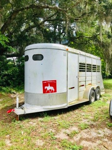 1999 WW (3) horse slant load bumper pull trailer with a front tack room that has saddle racks and bridle hooks.  The horse area has an interior height at 7' tall x 6' wide x 16' long, escape door, rubber mats over wood floor and a full swinging rear door.  The exterior has two 3500lbs axles and a spare tire.   Weighs 3500lbs.