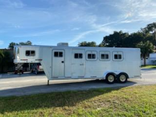 2000 Exiss (4) horse slant load gooseneck trailer with a front tack room that has an A/C unit, saddle racks, bridle hooks and a brush box.  The horse area has an interior height at 7' tall x 7' wide, escape door, drop down windows at the horses heads, sliding bus windows at the horses hips, roof vents, rubber lined walls, rubber mats over all aluminum floor and a rear collapsible tack room with double back rear doors!   Spare tire.